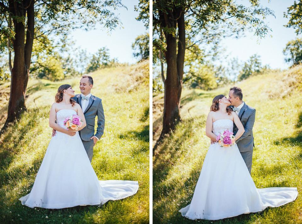 Ženich líbá nevěstu mezi stromy