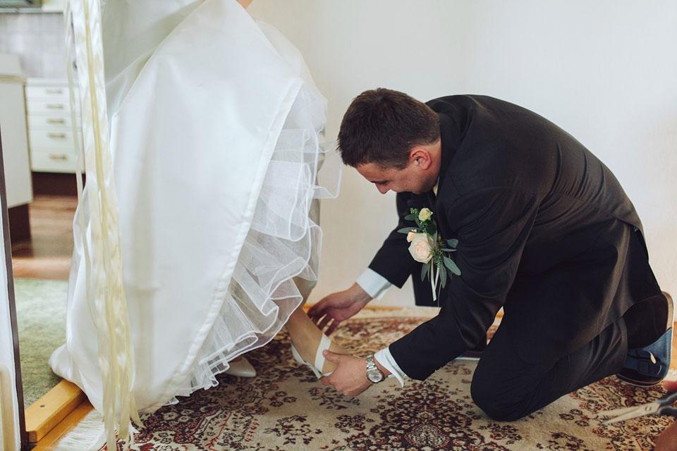 ženich obouvá nevěstě svatební střevíce